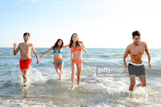 France, four young adults running in the sea in swimsuit.