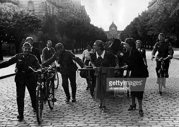 2WW France German occupation Strasbourg Female post office clerks return to their office German soldiers help pushing the luggage barrow Early July...