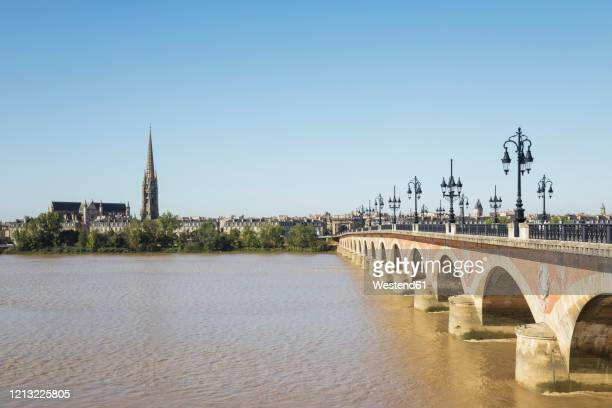 france, gironde, bordeaux, clear sky over pont de pierre with basilica of saint michael in background - ボルドー ストックフォトと画像
