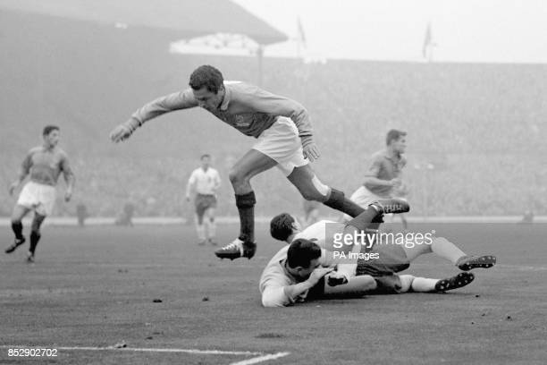 France goalkeeper Claude Abbes goes sprawling with England's Bobby Robson while France's Mustapha Zitouni jumps over the top during an England attack...