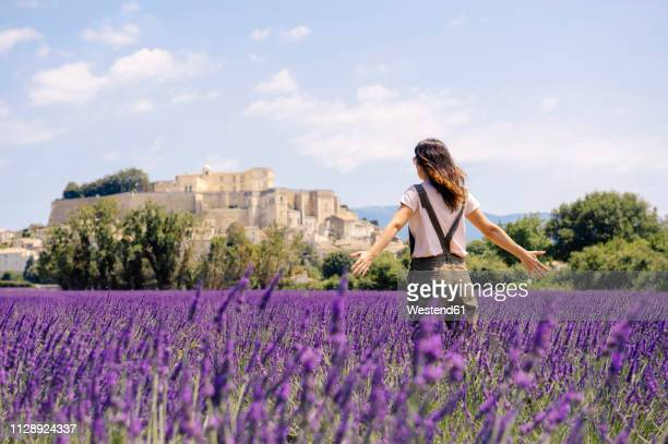 France, Grignan, back view of woman standing in lavender field looking at village