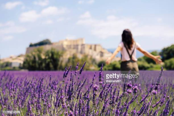 France, Grignan, back view of woman standing in lavender field