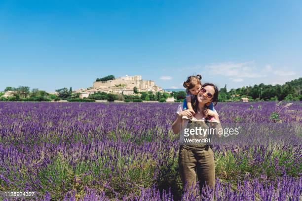 France, Grignan, happy mother carrying her little daughter through lavender field