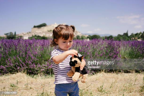 France, Grignan, portrait of baby girl with soft toy outdoors