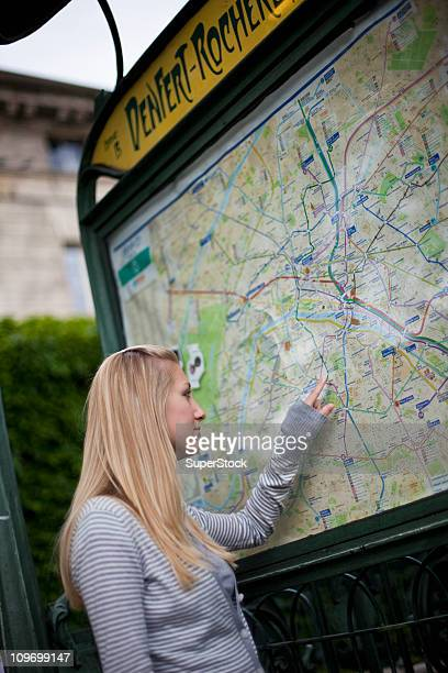 France, Ile-de-France, Paris, Teenage girl looking at Paris Metro map