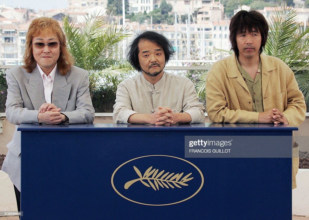 Japanese director Mamoru Oshii (C), composer Kawai Kenji (L) and producer Ishikawa Mitsuhisa pose during a photo call for his film 'Innocence', 20 May 2004, at the 57th Cannes Film Festival in the French Riviera town. The film is in competition for the festival's top prize, the Palme d'Or.