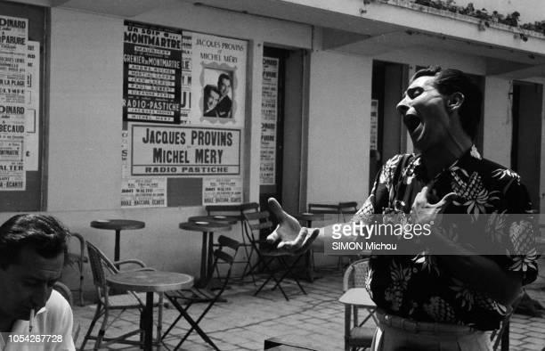 France Juillet 1955 Le chanteur français Gilbert BECAUD alias 'Monsieur 100000 volts' effectue une tournée estivale Ici debout en train de chanter à...