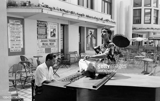 France Juillet 1955 Le chanteur français Gilbert BECAUD alias 'Monsieur 100000 volts' effectue une tournée estivale Ici assis sur un piano a queue en...