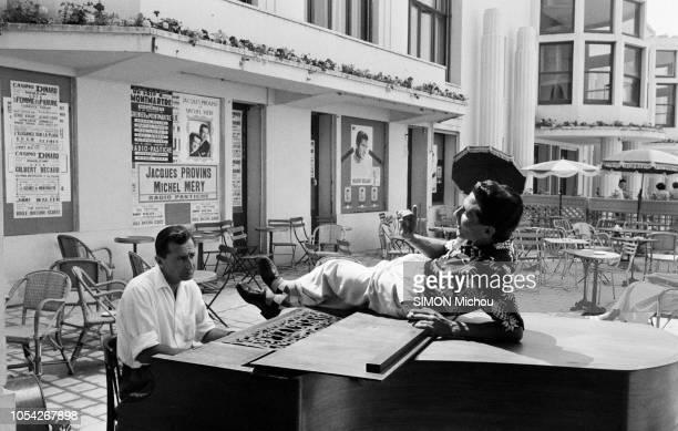 France Juillet 1955 Le chanteur français Gilbert BECAUD alias 'Monsieur 100000 volts' effectue une tournée estivale Ici allongé sur un piano a queue...