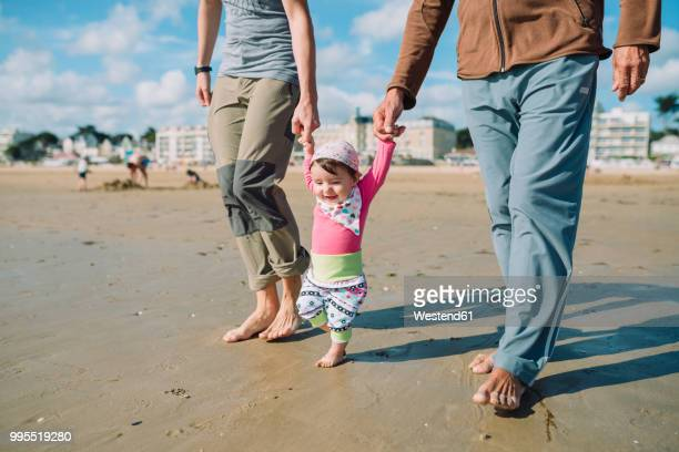 France, La Baule, baby girl walking on the beach with father and grandfather