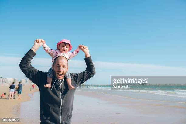 France, La Baule, portrait of father carrying his little daughter on shoulders on the beach