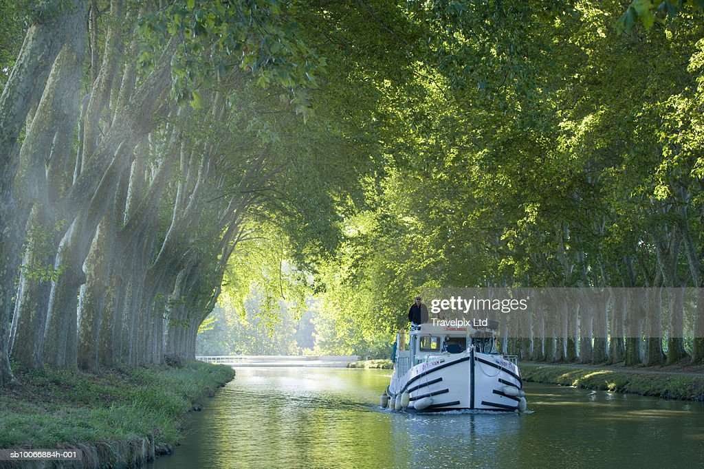 France, Languedoc, Carcassonne, boat in tree lined canal : Stock Photo