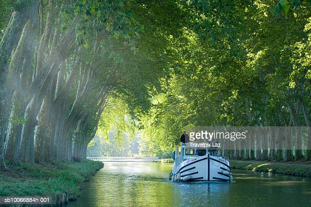 france, languedoc, carcassonne, boat in tree lined canal - canal du midi photos et images de collection