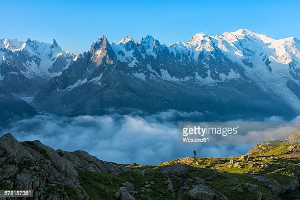 france, mont blanc, lake cheserys, hiker in front of mount blanc at sunrise - monte bianco foto e immagini stock