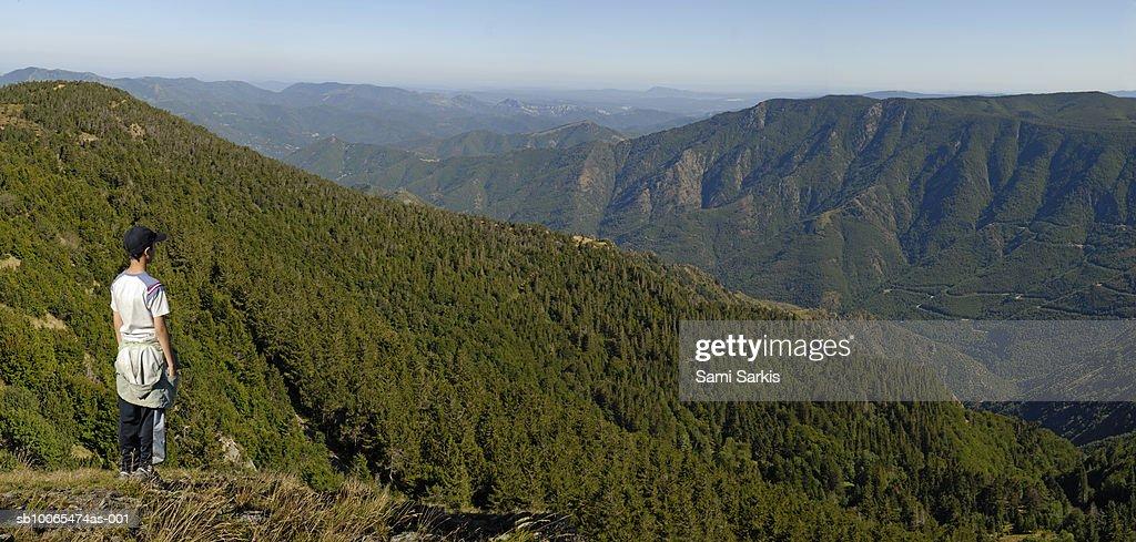 France, Mount Aigoual, Cevennes region, boy (12-13) looking at mountain range from Mount Aigoual : Stock Photo
