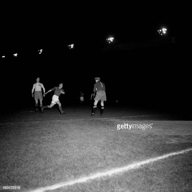 A France national soccer team player is in action while the Swede goalkeeper looks on during the friendly match FranceSwede on March 26 1952 at Paris...