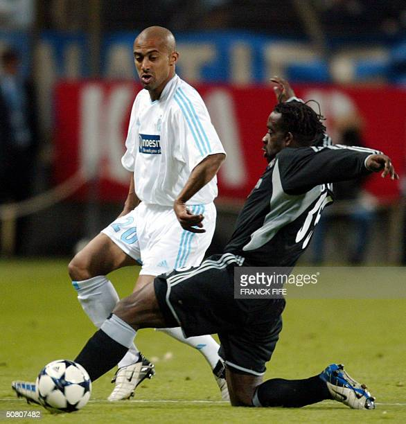 Newcastle's defender French Olivier Bernard vies with Marseille's French forward Steve Marlet during their UEFA Cup semifinal second leg football...