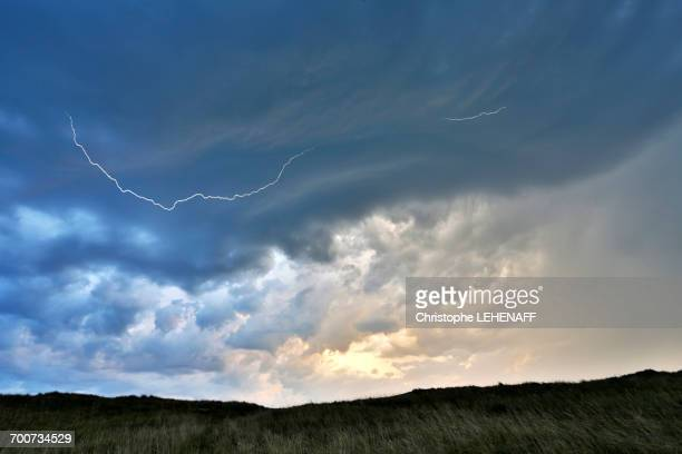 france, normandy. annoville. the dunes and the beach. beginning of a storm. lightning in the sky - cotentin photos et images de collection