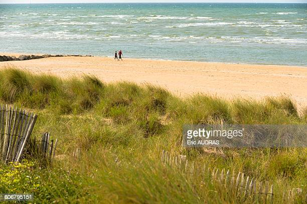 france, normandy, couple enjoying a walk along the sea on cabourg beach - calvados stock pictures, royalty-free photos & images