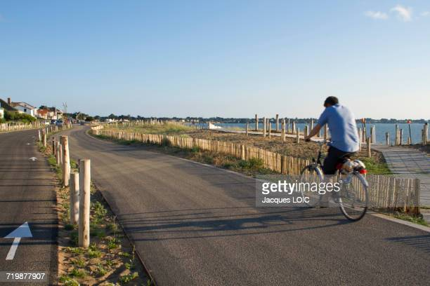 France, North-Western France, Saint-Michel-Chef-Chef, Tharon-plage, man riding a bike on the bicycle path along the sea