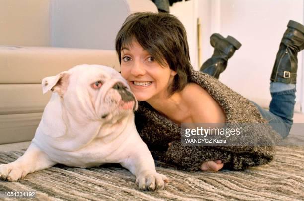 France Novembre 2003 L'humoriste Florence FORESTI grimaçant à plat ventre sur un tapis à côté de son bulldog anglais
