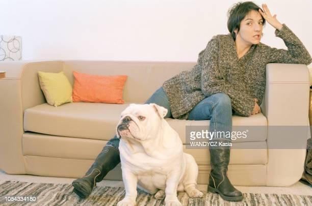 France Novembre 2003 L'humoriste Florence FORESTI s'appuyant sur l'accoudoir de son sofa avec son chien bulldog anglais à ses pieds