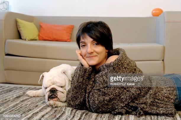 France Novembre 2003 L'humoriste Florence FORESTI souriant allongée à plat ventre sur un tapis à côté de son bulldog anglais endormi