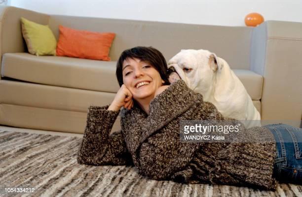 France Novembre 2003 L'humoriste Florence FORESTI souriant allongée à plat ventre sur un tapis avec son bulldog anglais
