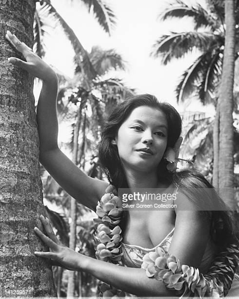 France Nuyen French actress posing beside the trunk of a palm tree wearing a lowcut top and a flower leis around her neck circa 1960