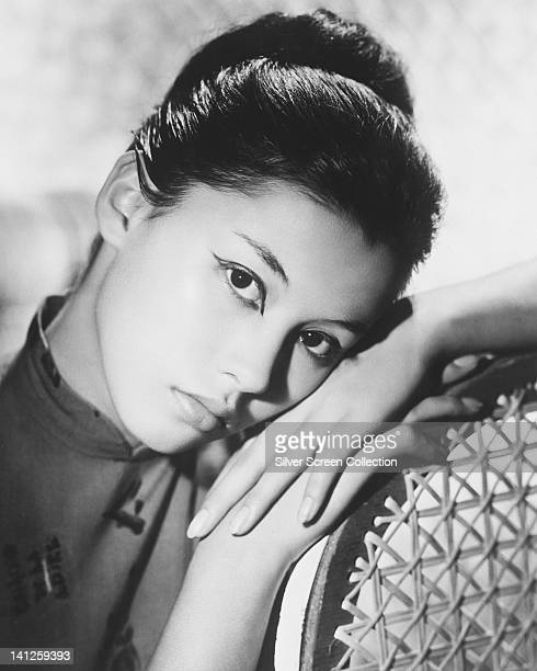 France Nuyen French actress resting her head on her hands which rest on the back rest of a canebacked chair in a studio portrait circa 1960