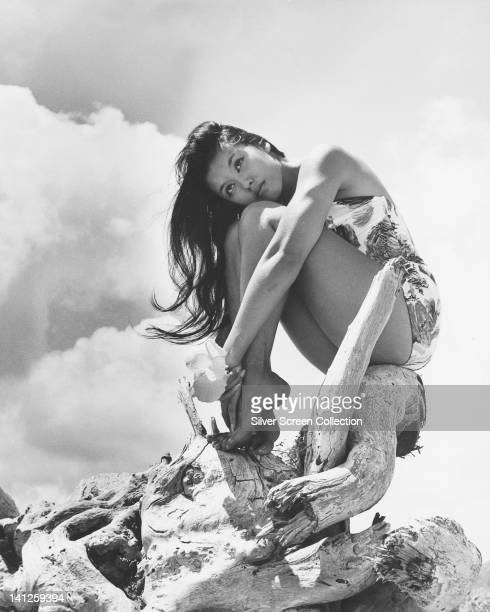 France Nuyen French actress wearing a print pattern swimsuit posing with her arms wrapped around her legs as she sits on a piece of driftwood circa...