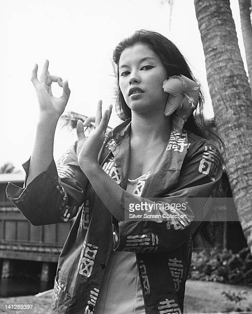 France Nuyen French actress with a flower in her hair wearing an open oriental blouse gesticulating with her hands circa 1960