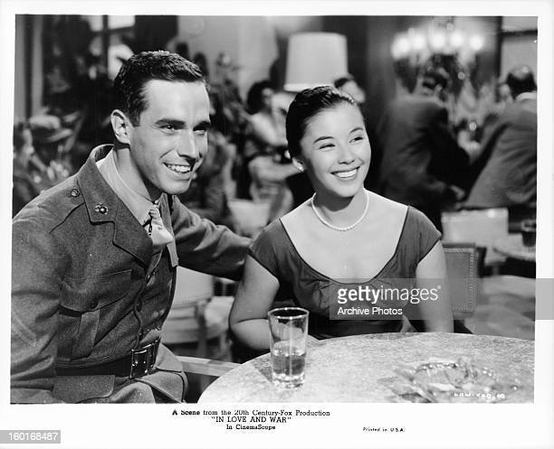 France Nuyen sitting at a table with a man in a military uniform in a scene from the film 'In Love And War' 1958