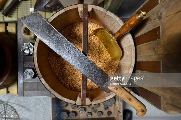 France, old machete lying on a wooden bucket containing grains of wheat. Copper shovel in grains
