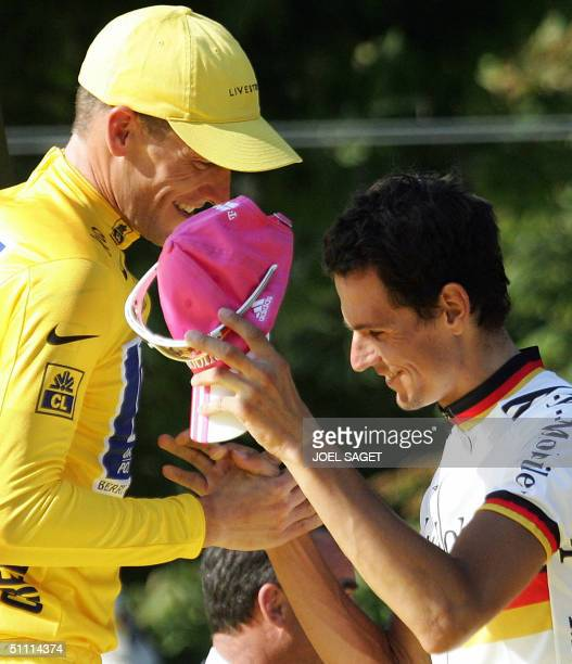 Overall leader US Lance Armstrong shakes hands with second placed German Andreas Kloden on the podium at the end of the 91st Tour de France cycling...