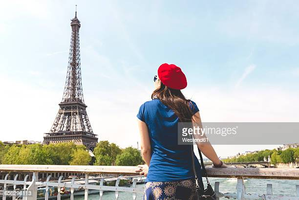 france, paris, back view of woman wearing red beret looking at eiffel tower - red hat stock pictures, royalty-free photos & images