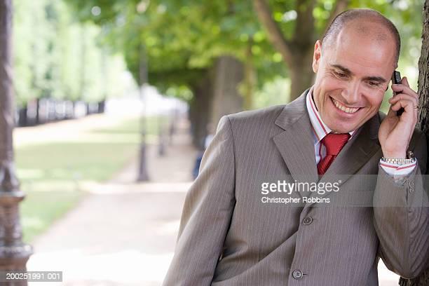 France, Paris, businessman on street using mobile phone, smiling