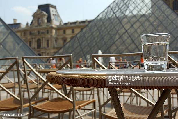 France, Paris, cafe table, Louvre Pyramid and Museum in background