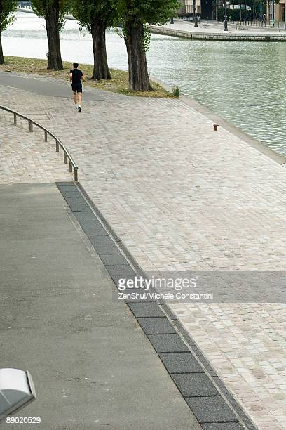 france, paris, canal saint-martin, person jogging along water's edge - quayside stock pictures, royalty-free photos & images