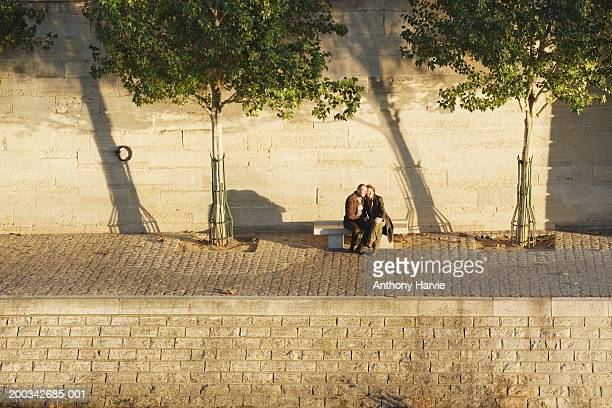 France, Paris, couple embracing on bench by River Seine, elevated view