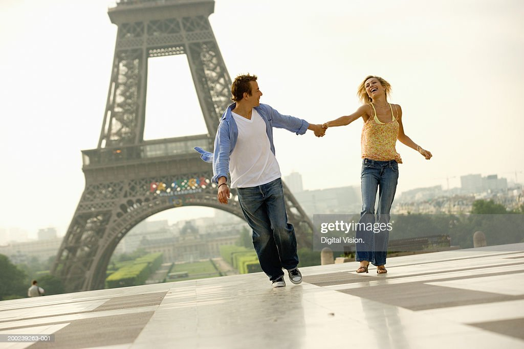 France, Paris, couple holding hands while running, smiling : Stock Photo