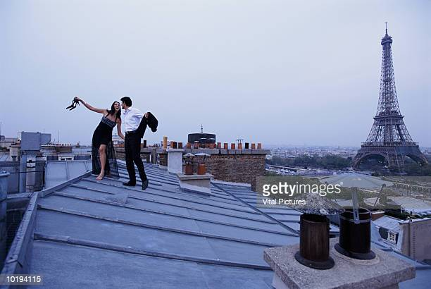 France, Paris, couple in formal wear on rooftop