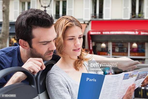 France, Paris, couple looking at a city map