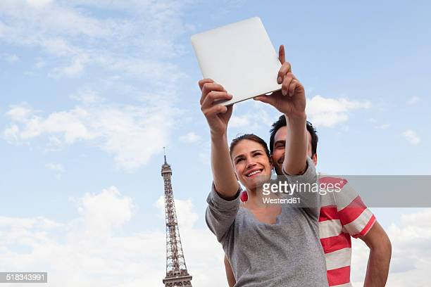 France, Paris, couple photographing themself with tablet computer in front of Eiffel Tower