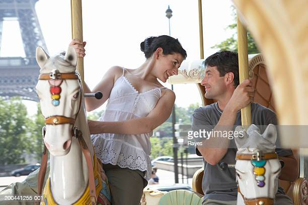 France, Paris, couple riding carousel, smiling at one another