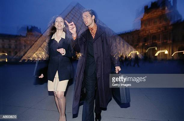 france, paris, couple walking through louvre courtyard, night - musee du louvre stock pictures, royalty-free photos & images