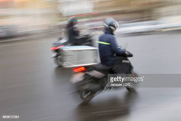 france, paris, couriers by scooter. - moped stock photos and pictures
