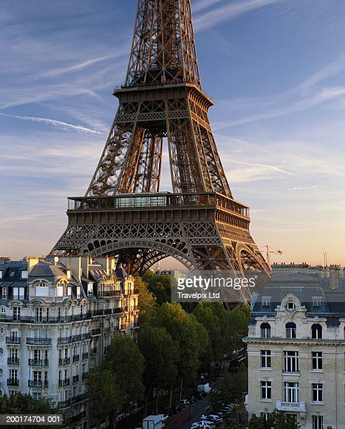 france, paris, eiffel tower amongst city buildings, sunset - travel14 stock pictures, royalty-free photos & images