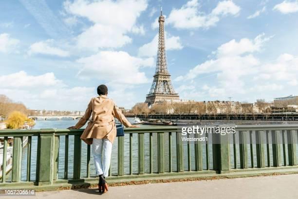 france, paris, female tourist looking towards the eiffel tower and the seine river - garde corps photos et images de collection