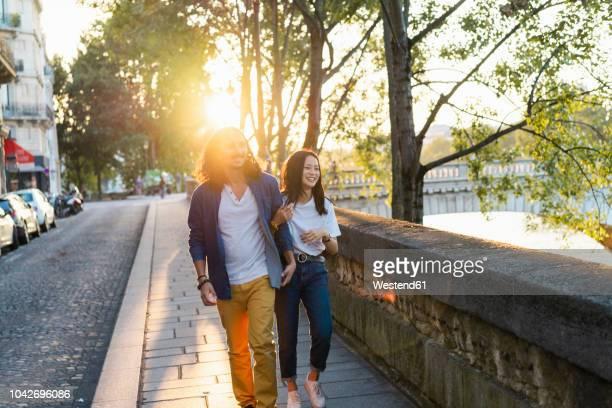france, paris, happy young couple walking at river seine at sunset - lichtvlek stockfoto's en -beelden